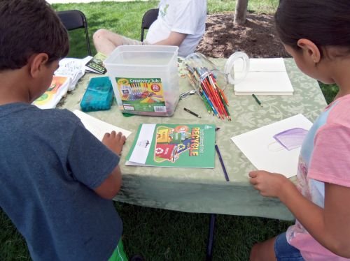 Children busy drawing with crayons, colored pencils and markers.