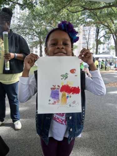 Little girl holds up her frog art drawing at WPLIVE