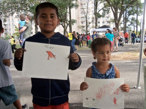 Children pose with their frog art in the Frogs Are Green tent at WPLIVE