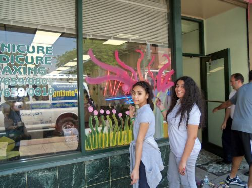 students painting windows on Central Avenue shop for City of Trees initiative