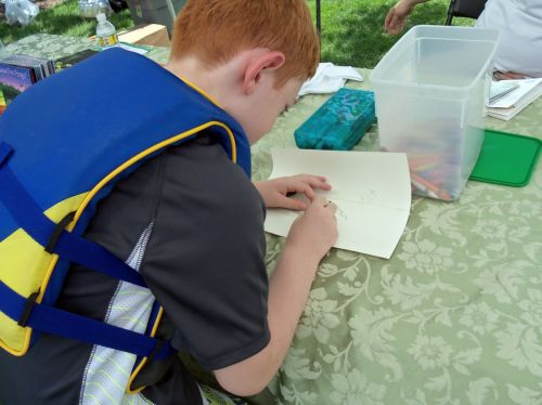 Child drawing frogs under the Frogs Are Green tent at The City of Water event in Hoboken.