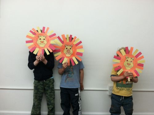 Boys create lion masks from colored paper in Peaceful Frogs class in Hoboken with Susan Newman